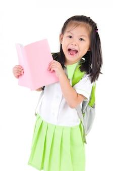 Gelukkig weinig schoolmeisje met boeken die op witte achtergrond worden geïsoleerd