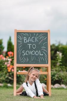 Gelukkig weinig schoolmeisje met een bord buiten