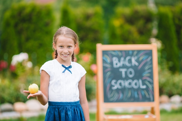 Gelukkig weinig schoolmeisje met een schoolbord buiten