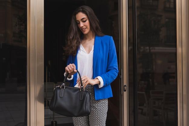 Gelukkig werknemer houden van de mobiele telefoon in haar handtas