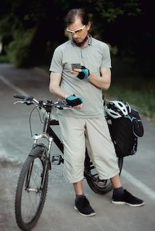 Gelukkig wielrenner in een gele zonnebril met behulp van mobiele telefoon in park, mooie zonnige dag