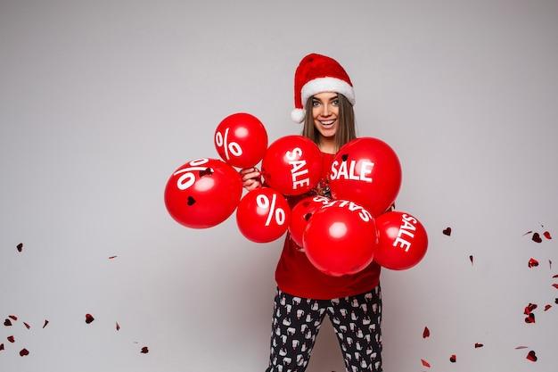 Gelukkig wijfje in rood t-shirt en comfortabele broek met rode en witte kerstmuts