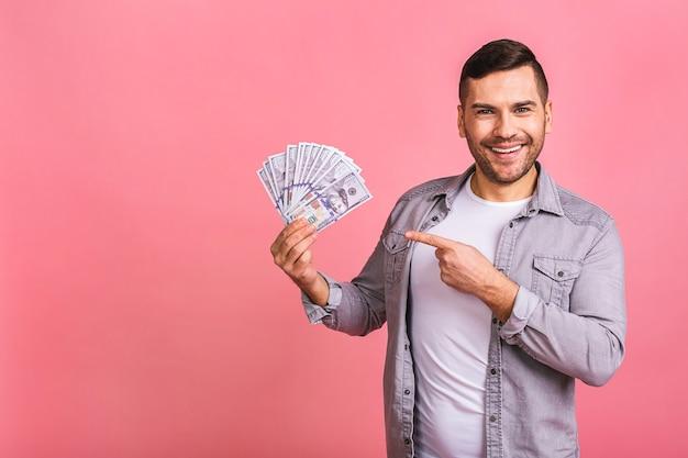 Gelukkig winnaar jonge rijke man in casual bedrijf geld dollarbiljetten met verbazing
