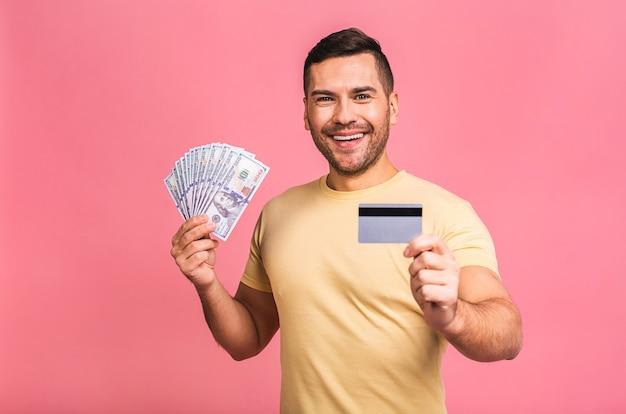 Gelukkig winnaar jonge verrast rijke man in casual bedrijf geld dollarbiljetten en creditcard