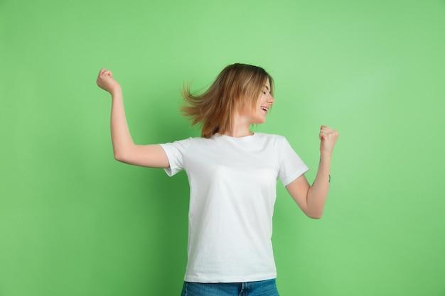 Gelukkig winnen. portret van de blanke jonge vrouw geïsoleerd op groene studio wall
