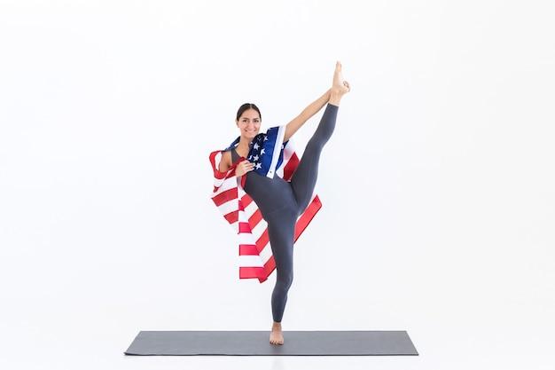 Gelukkig yogi vrouw doet yoga-oefeningen permanent met amerikaanse vlag, bindgaren pose. 4 juli vs onafhankelijkheidsdag concept