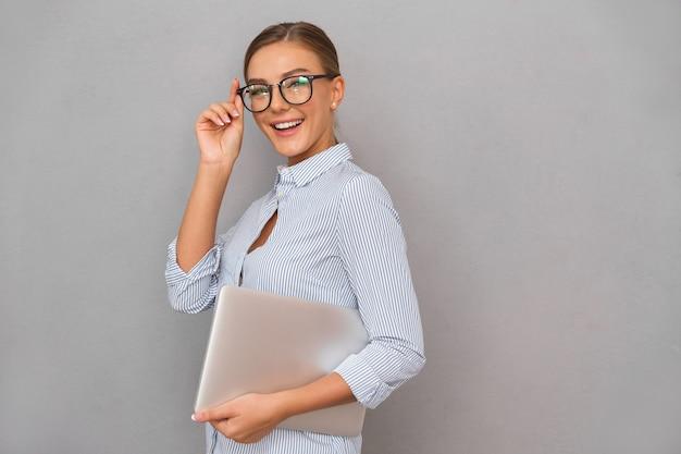 Gelukkig zaken jonge vrouw poseren geïsoleerd over grijze muur achtergrond bedrijf laptopcomputer.
