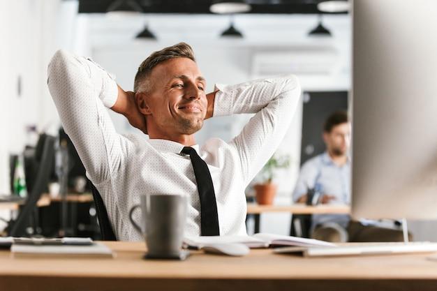 Gelukkig zaken man zitten in kantoor werken met computer hebben een rust.