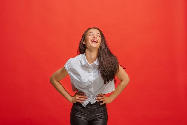 Gelukkig zaken vrouw permanent en glimlachend geïsoleerd op rood. mooi vrouwelijk portret van halve lengte.
