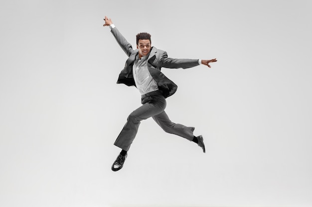 Gelukkig zakenman dansen in beweging geïsoleerd op witte studio achtergrond. flexibiliteit en gratie in het bedrijfsleven. menselijke emoties concept. office, succes, professioneel, geluk, expressieconcepten