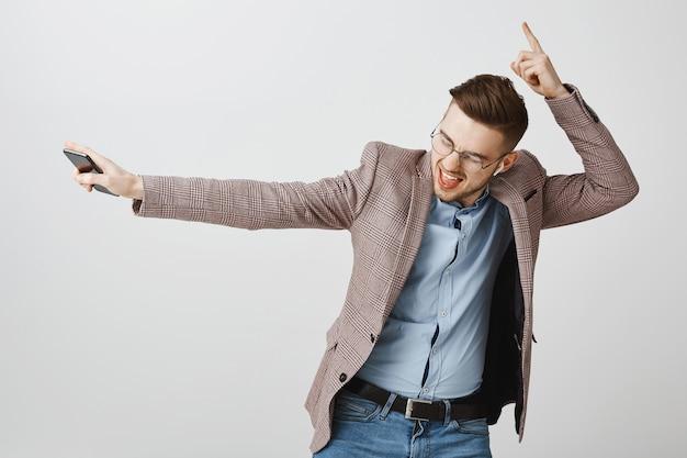 Gelukkig zakenman dansen in vreugde met smartphone, muziek luisteren in draadloze oortelefoons