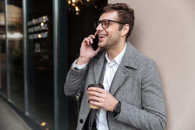 Gelukkig zakenman in brillen en jas praten door smartphone