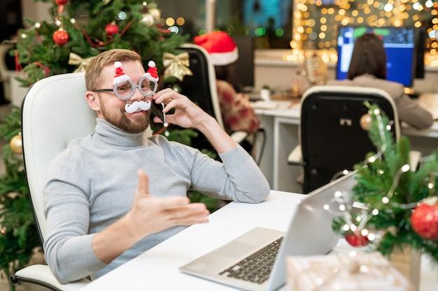 Gelukkig zakenman in xmas bril feliciteren met zakenpartners aan de telefoon voor laptop in kantoor