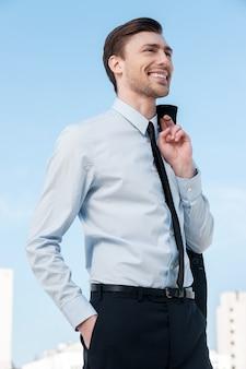 Gelukkig zakenman. knappe jongeman in formele kleding die zijn jas om zijn vinger houdt en wegkijkt terwijl hij tegen de blauwe lucht staat