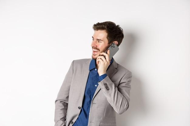 Gelukkig zakenman lachen en glimlachen, praten op mobiele telefoon, hand in zak houden en opzij kijken naar lege ruimte met vrolijk gezicht
