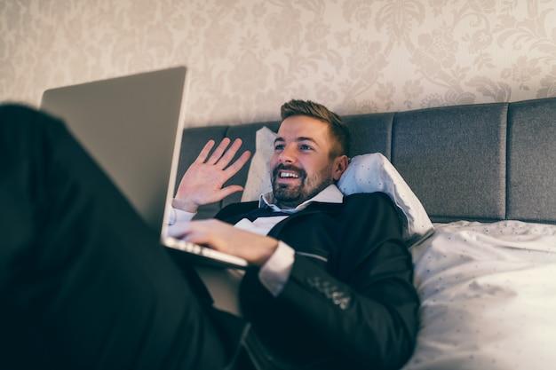 Gelukkig zakenman liggend op het bed in hotelkamer in pak en met behulp van laptop voor videogesprek.