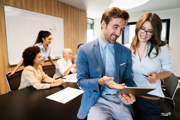 Gelukkig zakenman met collega's die werken op een conferentie op kantoor