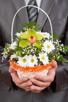 Gelukkig zakenman met mand met bloemen