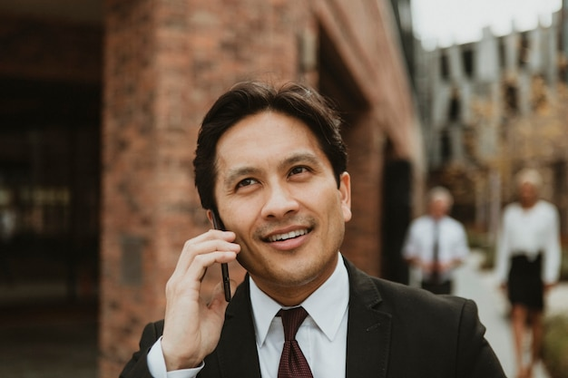 Gelukkig zakenman praten aan de telefoon in het centrum