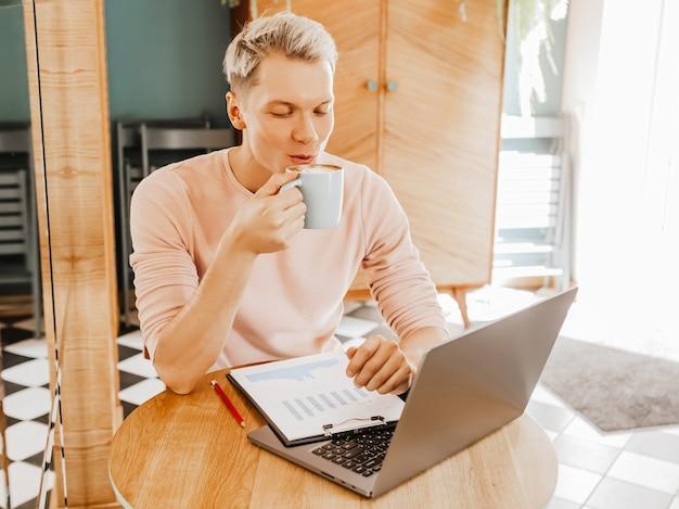 Gelukkig zakenman zit in cafetaria met laptop en smartphone. zakenman zit in een café