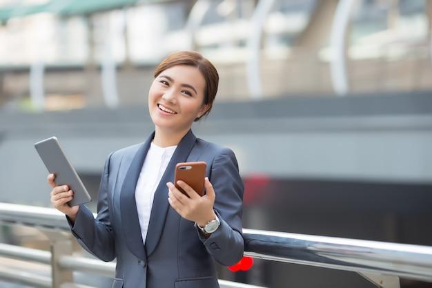 Gelukkig zakenvrouw gebruik tablet en smartphone