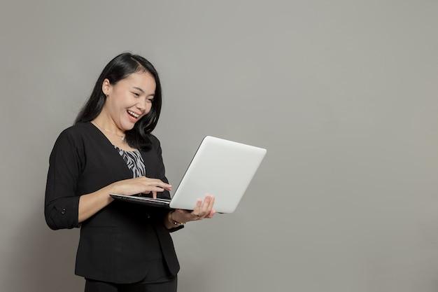 Gelukkig zakenvrouw houden en kijken naar laptop scherm