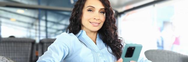 Gelukkig zakenvrouw in afwachting van haar bestelling in een restaurant met een telefoon in haar hand. jonge vrouwelijke werknemer glimlacht tijdens een pauze
