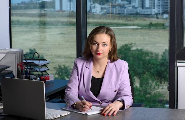 Gelukkig zakenvrouw in slimme vrijetijdskleding zittend aan de kantoortafel en kijkt naar de camera op kantoor. portret van mooie brunette glimlachende vrouw in zakelijk paars pak schrijft in een notitieboekje