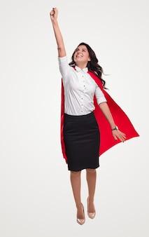 Gelukkig zakenvrouw in superheld cape vliegen