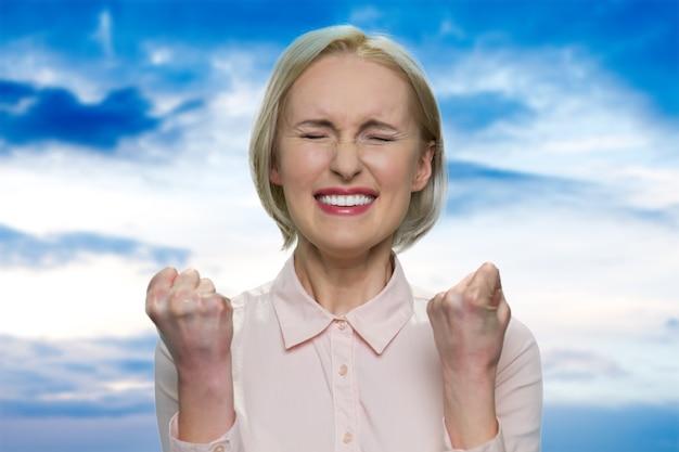 Gelukkig zakenvrouw in witte blouse is blij. geluk en succes concept. blauwe lucht op de achtergrond.