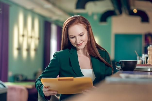 Gelukkig zakenvrouw kijken naar documenten in map