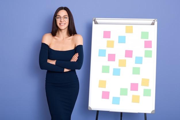Gelukkig zakenvrouw poseren in de buurt van flip bord met stickers, houdt armen gevouwen, poseren met blote schouders geïsoleerd op blauwe achtergrond, met positieve emoties.