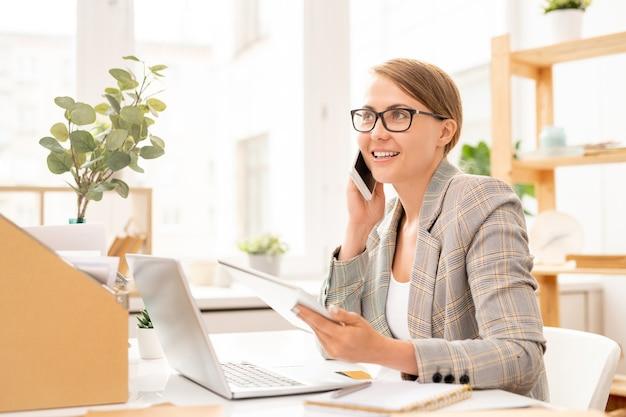 Gelukkig zakenvrouw praten door smartphone en het gebruik van tablet voor laptop zittend door het bureau in kantoor