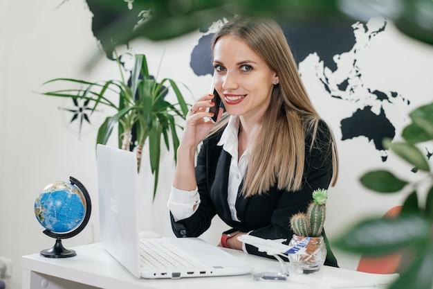 Gelukkig zakenvrouw reisbureau met behulp van laptop en smartphone voor communicatie en online werken in een moderne omgeving met planten, vlucht boeken. reisbureau regelt rondreis