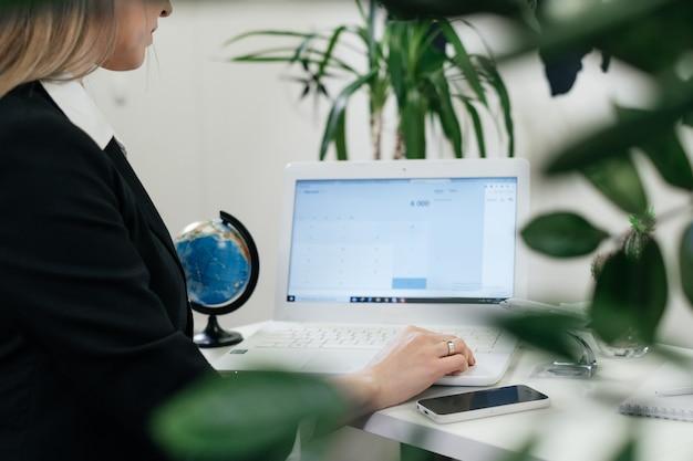 Gelukkig zakenvrouw reisbureau met behulp van laptop voor communicatie en online werken in een moderne omgeving met planten, vlucht boeken. reisbureau regelt rondreis over de hele wereld