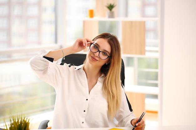 Gelukkig zakenvrouw werken in kantoor met documenten