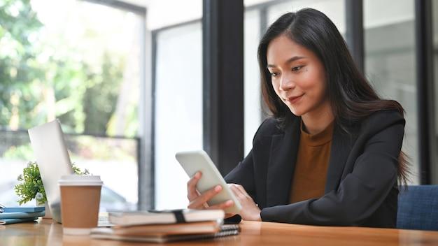 Gelukkig zakenvrouw zittend op een moderne werkplek en het gebruik van mobiele telefoon.
