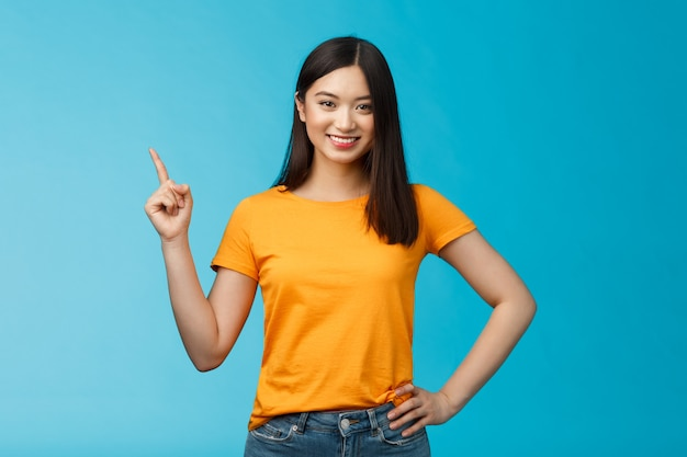 Gelukkig zelfverzekerd aziatisch meisje zelfverzekerd wijzend naar de linkerbovenhoek, de weg wijzen, vastberaden glimlachen, assertief introduceren online winkel promo, blauwe achtergrond in geel t-shirt staan. ruimte kopiëren