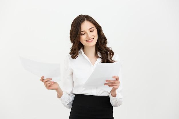 Gelukkig zelfverzekerd jonge blanke vrouw met rapport papier staande glimlachend geïsoleerd