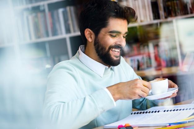 Gelukkig zelfverzekerde jonge man die werkt, studeert en een koffiepauze heeft