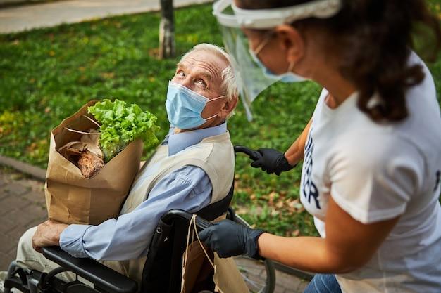 Gelukkig zelfverzekerde man in blauw shirt in rolstoel die tijd doorbrengt met vrouwelijke vrijwilliger