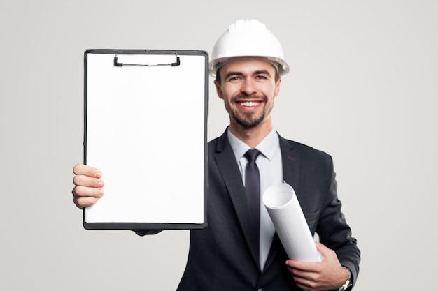Gelukkig zelfverzekerde mannelijke ingenieur in formeel pak en veiligheidshelm met opgerolde blauwdruk in de hand die klembord demonstreert met leeg wit vel papier