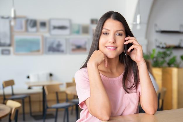 Gelukkig zelfverzekerde mooie jonge vrouw praten over cel, staande op co-working, leunend op bureau,