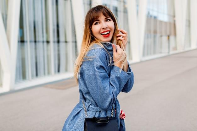 Gelukkig zelfverzekerde vrouw wandelen langs moderne straat in stijlvolle blauwe wollen jas