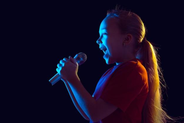 Gelukkig zingen. kaukasisch meisje portret op donkere studio achtergrond in neonlicht. mooi vrouwelijk model met speaker.
