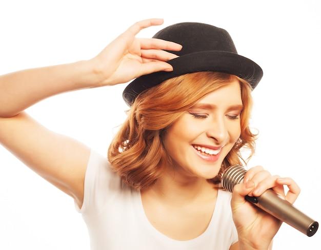 Gelukkig zingend meisje. schoonheid vrouw, gekleed in witte t-shirt en zwarte hoed met microfoon over wit. hipster-stijl.