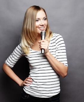 Gelukkig zingend meisje. schoonheid vrouw t-shirt met microfoon dragen over grijze ruimte.