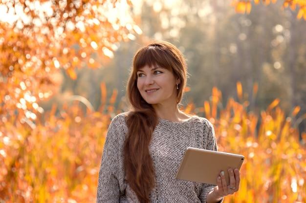 Gelukkig zittende vrouw met behulp van tablet tijdens herfst wandelingen buiten in park. telewerken, onderwijsconcept. kopieer ruimte