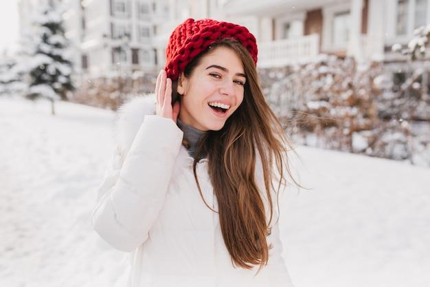 Gelukkig zonnige bevroren ochtend op wintertijd van vrolijke jonge vrouw in rode hoed, met lang donkerbruin haar plezier op straat vol met sneeuw.