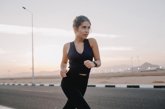 Gelukkig zonnige ochtendmomenten van hardwerkende gemotiveerde geweldige jonge vrouw in sportkleding draait op weg in het vroege ochtendvn tropisch land. training, training, gezonde levensstijl
